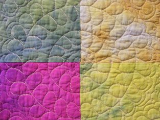 featured is a macro photo of a section of an antique quilt by us joy